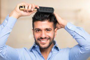 man brushing his full head of hair after a Follicular Unit Transplant at Men's Health Atlanta