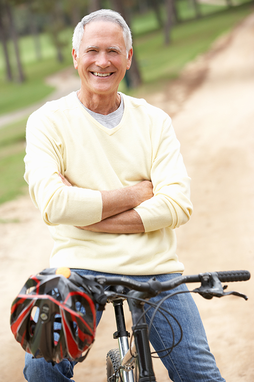 photo of a senior man riding bicycle in park